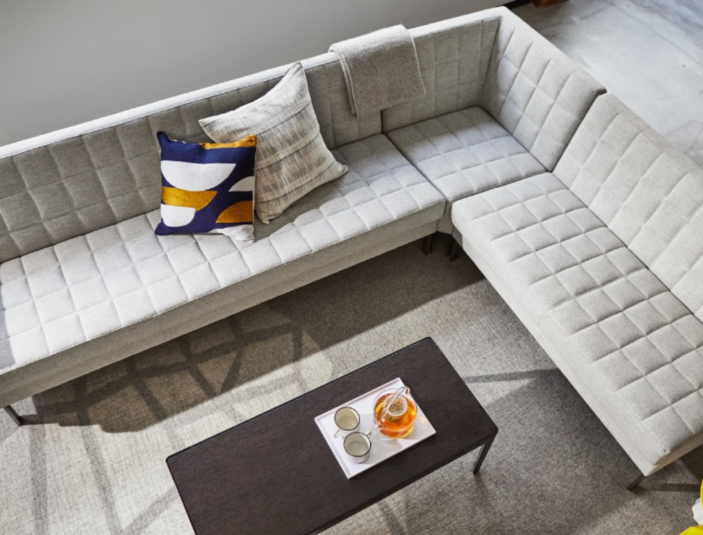 Grey office sectional couch in lounge space with wooden office table and grey carpeting