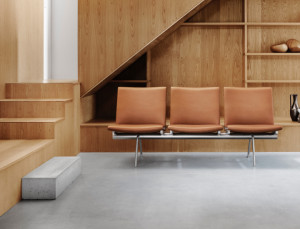 Wood-paneled reception area in office with brown bench seating and decorative shelves