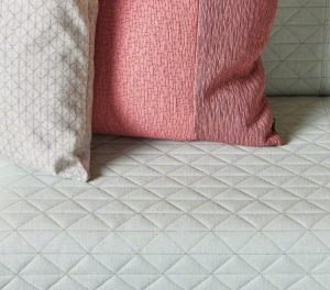 Detail of couch upholstery diamond-shaped stitching with throw pillows