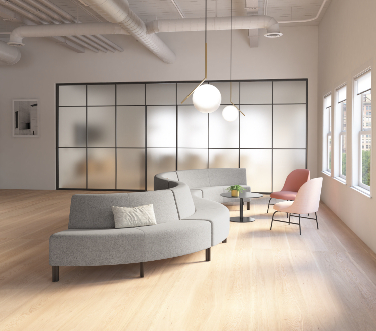 Lounge space in office with connected grey sectional couch, round side table, and pink side chairs