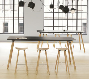 Long grey office conference table with wooden legs and matching stools in front of an arched window
