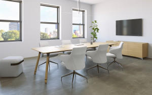 Long wooden conference table with white conference chairs, matching armrest, wooden storage credenza, and wall-mounted monitor