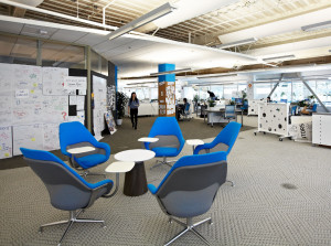 Informal office gathering space with blue chairs and small round table near meeting room and work areas
