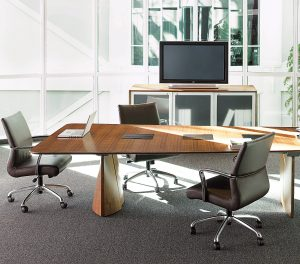 Office meeting space with plush leather chairs, grey carpeting, and long wooden conference room table