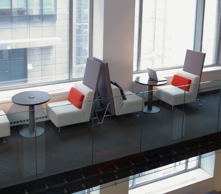 Office lounge bench seats with round tables and privacy screens in common area by windows