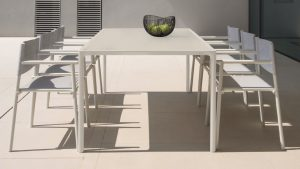Outdoor office dining space with fabric-backed outdoor chairs and tall outdoor dining table