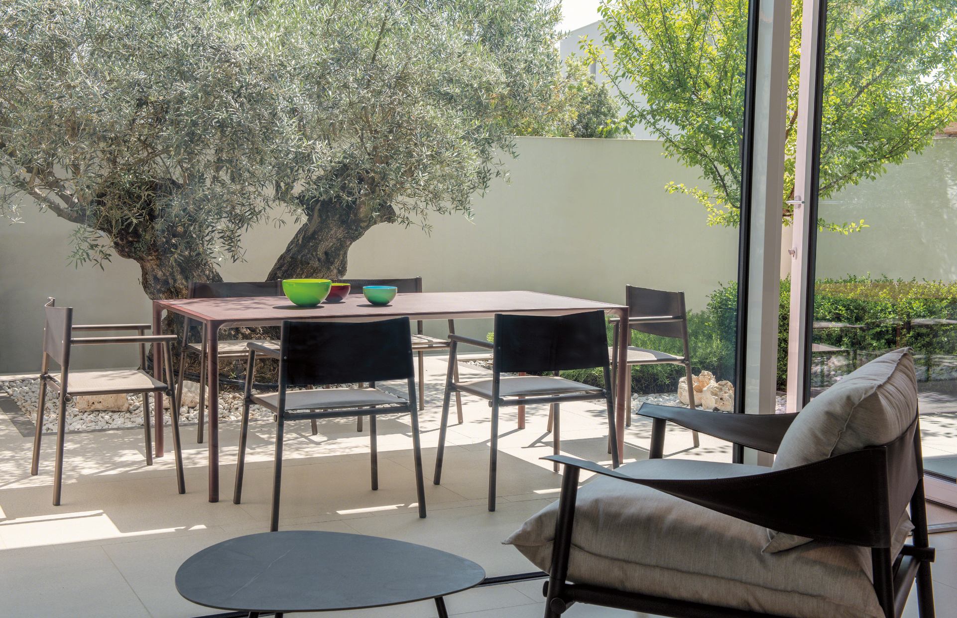Outdoor pation lounge with chairs, long table for dining, and round side tables