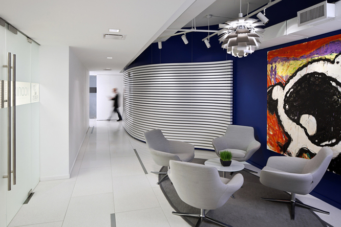 Small white table surrounded by grey lounge chairs on a circular dark grey rug, dark blue walls and a giant painting