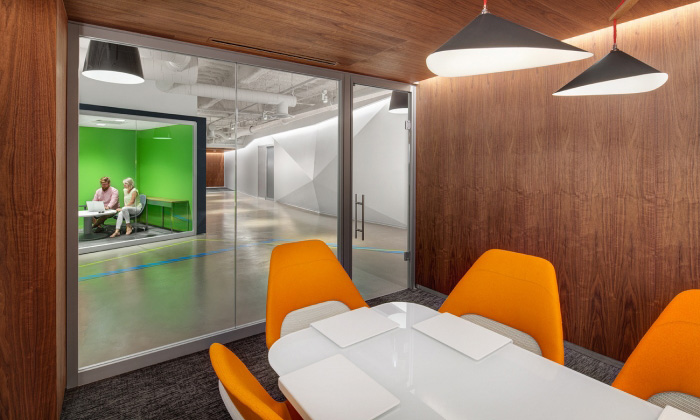 Enclosed conference room with white rectangular table, orange office chairs and interior glass windows and door looking out into a hallway