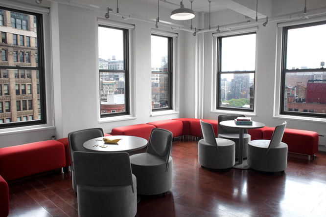 Two round metal tables with black round chairs in a room with dark hardwood floors and windows overlooking the city
