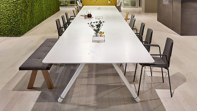Large white conference table with black office chairs and black cushioned bench on light hardwood floors.