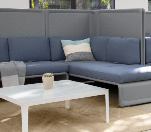 Two corner sectional couches, divided by high privacy screens, inside office lounge area with matching tables and chairs