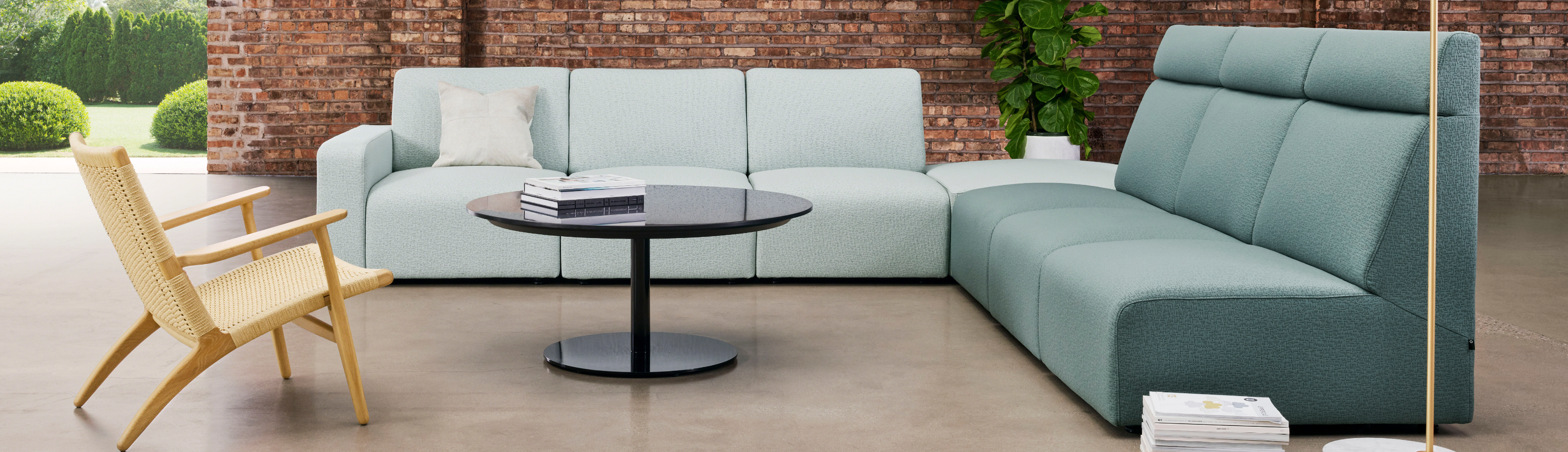 Blue office corner sofa in outdoor lounge space with mirrored black coffee table and wooden side chair