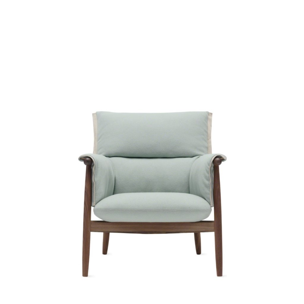 Plush lounge chair with light blue upholstered cushions and stained wood frame, armrest, & legs