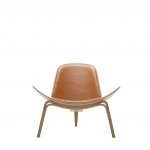 Shell lounge chair with modern curved base, light brown leather upholstery, and modern 3 leg base in light wood